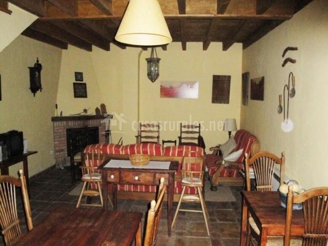 Salón con chimenea en la esquina y muebles de madera de la casa rural