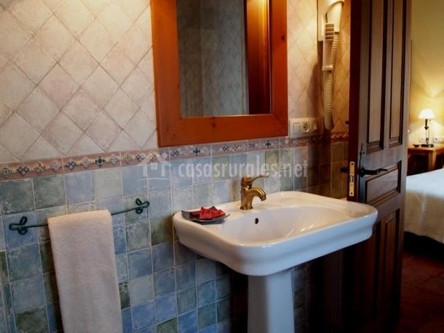 Baño Azul Con Blanco: azul con mosaico grande y espejo de madera sobre el lavabo blanco
